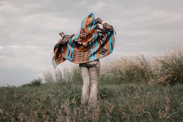 Beautiful boho woman wearing poncho on green field at sea shore