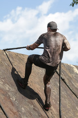 Mud race runners,participant for overcoming barriers through ropes
