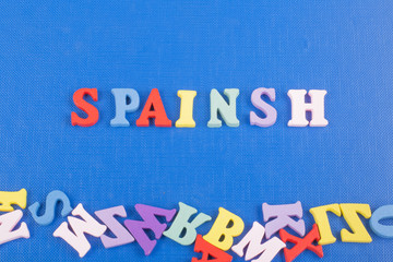 Spainsh word on blue background composed from colorful abc alphabet block wooden letters, copy space for ad text. Learning english concept