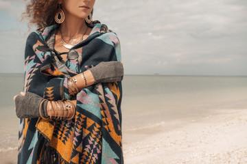 Beautiful young woman wearing poncho on the beach
