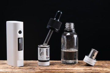 vaping set and liquid with  on a dark background