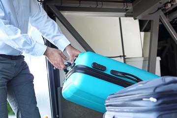 Walizki w luku bagażowym autokaru turystycznego.Kierowca wyjmuje bagaże