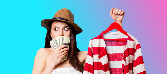 beautiful young woman with striped jacket on hanger and money standing in front of wonderful blue background
