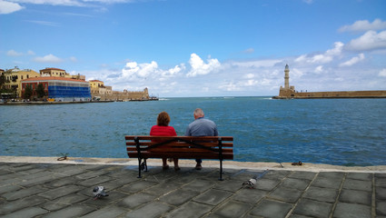 An elderly couple sitting on a bench on the promenade and admire the views in the center of Chania