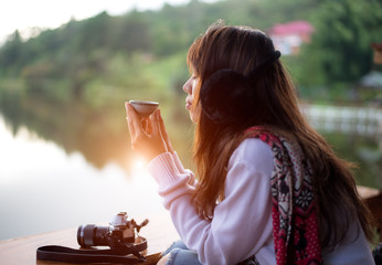 Young woman's hand holding cup of tea on a cold and morning day
