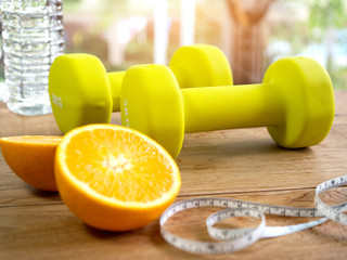 Dumbbells,orange, bottle of water and measuring tape for fitness.