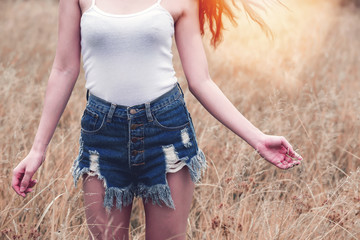 cropped image of young woman in white tank top and short blue jeans standing out door