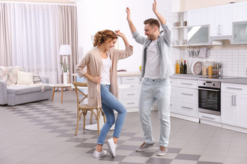 Cute young couple dancing at home