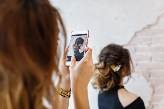 Woman hairdresser taking picture on smartphone of her client hairstyle