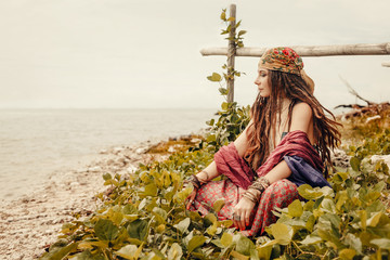 gypsy style young woman sitting on grass at the beach