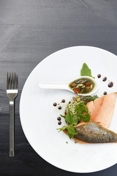 Plate of salmon fillets with fresh herbs, vegetables and balsamic vinegar on a black table