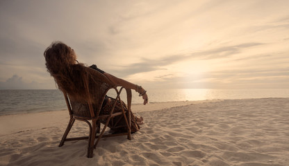 young woman relaxing in a chair on the beach at sunset