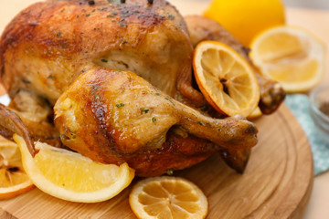 Homemade baked chicken with lemon on wooden board, closeup
