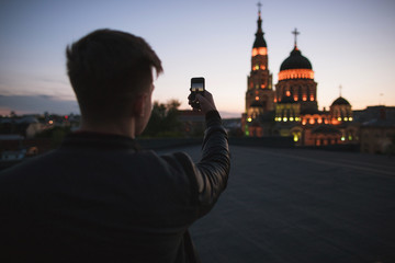 Traveler takes pictures of the city on a phone. Tourist near attractions. Guy uses a digital gadget for photos