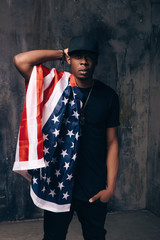 Confused afro american man with american flag on dark background. Patriot, immigration, independence day, social problem, usa citizen concept