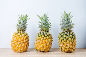 Ripe pineapples on a wooden table background.