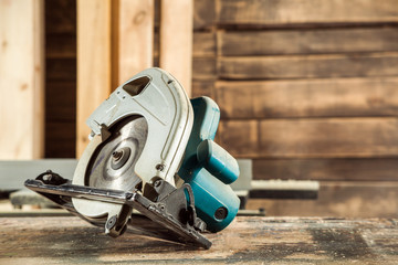 A modern green circular saw lies on a wooden table in the workshop. A close-up of a circular saw Wall mural