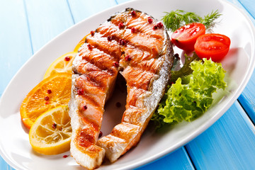 Grilled salmon with vegetables on blue wooden table