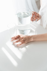 Cropped photo of lady sitting indoors near water jug