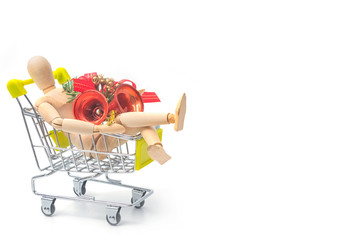 Wooden dummy holding gift box in shopping cart, shopping concept