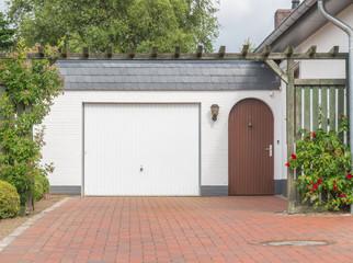 Garage mit weißem Tor und brauner Tür
