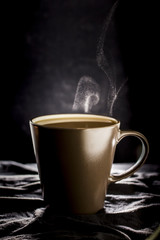 brown cup Coffee with a smoke   blck background