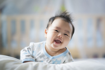 Newborn boy smile on the bed