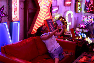 A woman takes a picture of neon signs while sitting on a sofa in God's Own Junkyard gallery and cafe in London, Britain