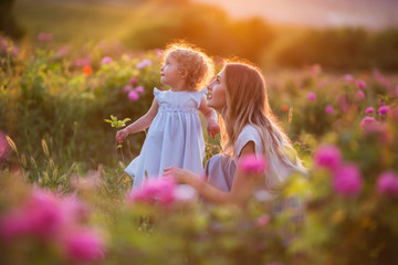 Beautiful child girl with young happy mother are wearing casual clothes walking in roses garden over sunset lights