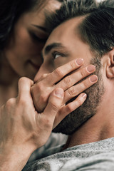 Close-up view of bearded handsome man kissing hand of sensual young woman