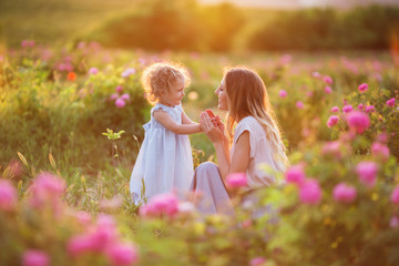 Beautiful child girl with young happy mother are wearing casual clothes walking in roses garden over sunset lights, summer time