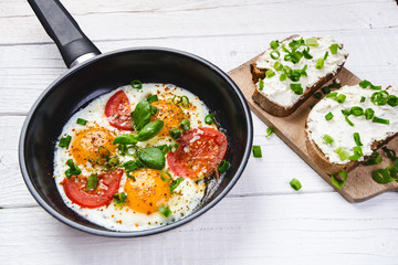 Pan of fried eggs with tomatoes, cheese, spring onion, herbs on a white table. Bread with spread. White wooden table. Concept of food. Breakfast time. Copy space.