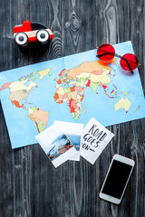 tourist outfit and mobile with map for trip with kids dark wooden background top view mockup