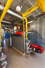 The interior of a modern gas boiler house with boilers, pumps, valves and a multitude of sensors
