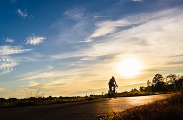 Silhouette of cyclists riding   bikes  on road at sunset.
