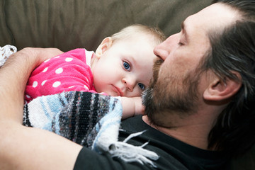 Daughter resting on sleeping father, portrait