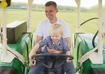 Mature man sitting with son in tractor, smiling