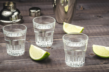 shot glasses with alcohol and a lime/shot glasses with alcohol and a lime on bar