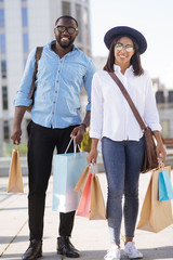 Young active couple seeming satisfied with their purchases