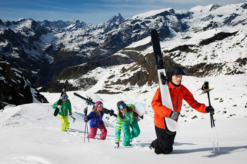 Group of skiers climbing mountain with ski equipment