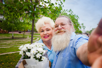 elderly couple walking around the park with a bouquet of flowers and make selfie