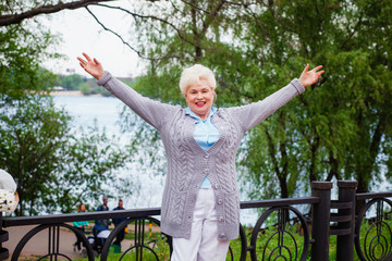 Old gray-haired beautiful woman opened her arms in the park