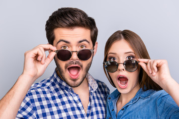 Really?! Two young shocked lovers are amazed with wide open eyes, mouthes, fixing sunglasses, in a casual wear on light background