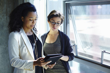 Two businesswomen looking at digital tablet in office