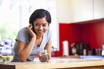Young woman using cellular phone in kitchen