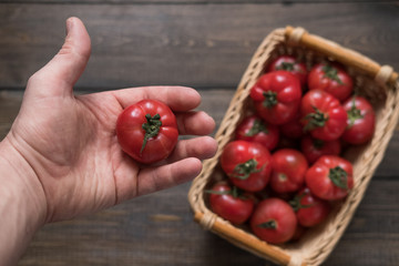 a basket of ripe tomatoes on a wooden background