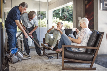 Two senior men vacuming house together while their wifes watching