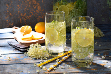 Elderberry flowers and lemon drink. Refreshment healthy elder juice. Glass of elderflower lemonade on wooden rustic board. Alternative medicine and therapy
