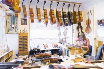 Luthier making violin in workshop