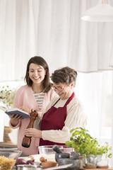 Granddaughter reading grandmother recipes